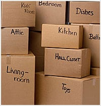 moving boxes piled up with their respective area written on the box